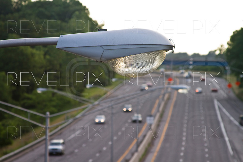 a close up shot of a highway light with traffic in the background.