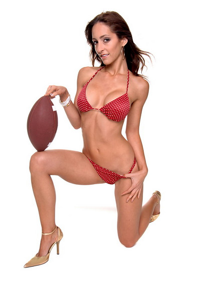 Beautiful young brunette in a bikini and posed with a football on her knee