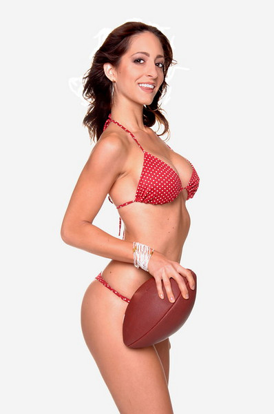 Beautiful young brunette in a bikini and standing and posed with a football