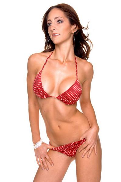 Beautiful young brunette in a red polka dot bikini with her thumbs hooked in the bikini bottoms