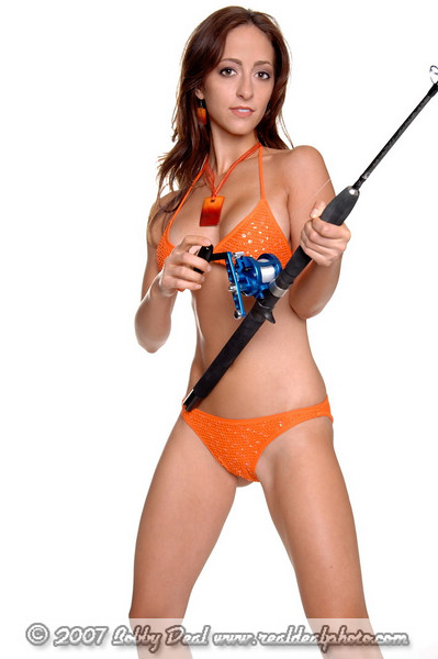 Beautiful young brunette in an orange sequine and beaded bikini with an orange shell necklace reeling in a fishing pole