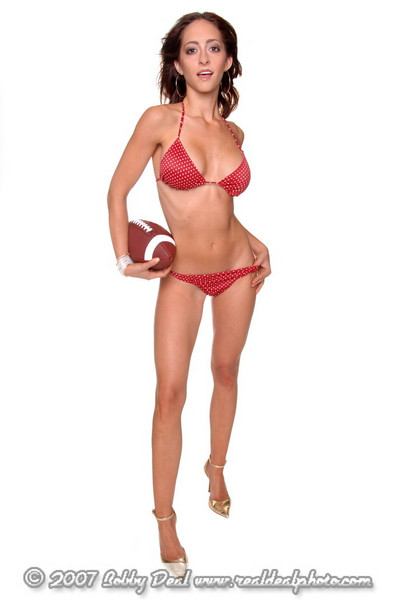 Beautiful young brunette in a bikini and posed with a football