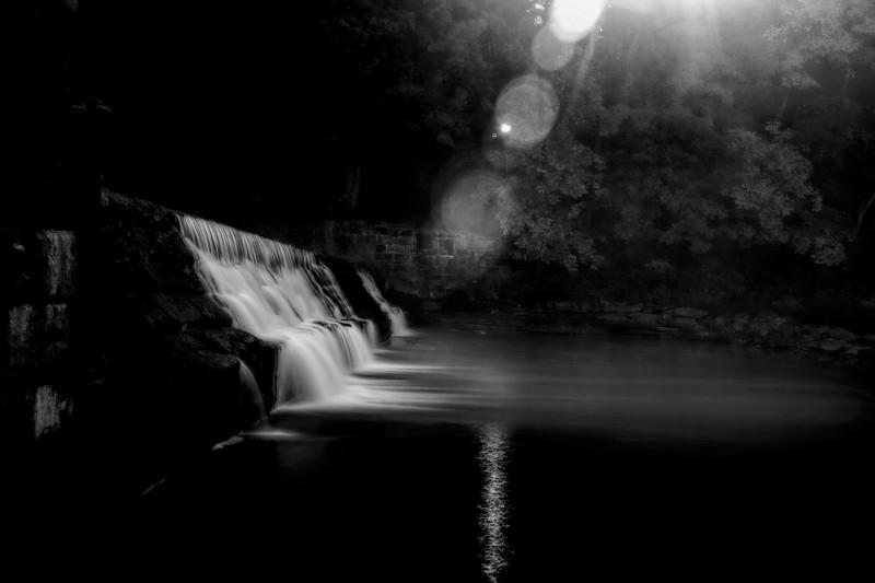 Sunburst at dam on river    Black and White