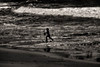 Child running in the ocean with sand bucket