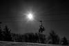 On ski lift heading up mountain black and white silhouette