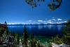 Lake Tahoe scene with puffy clouds and snow on mountains