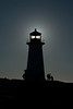 silhouette of lighthouse with sun