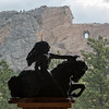 Model of Crazy Horse in front of mountain being carved