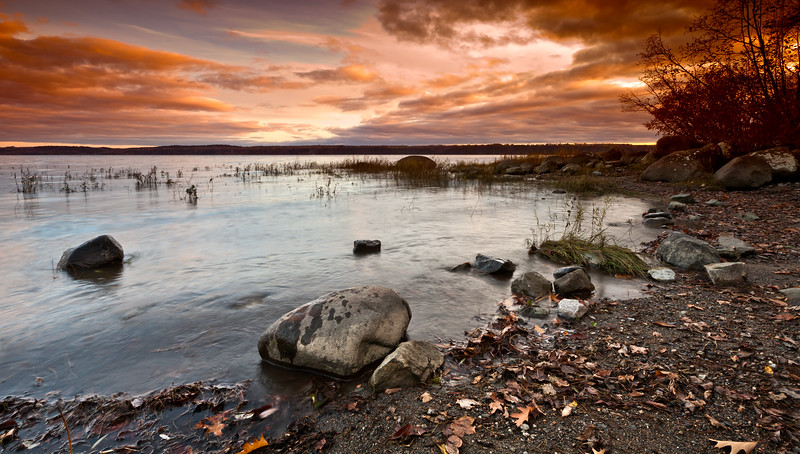 Beautiful landscape scene from a shore in Quebec canada. Moving water with orange sky and clouds.
