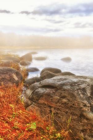 Beautiful autumn scene with fog and warm morning light. Canadian coast landscape.