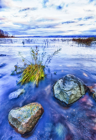 Fall scene with moving water, stone rock and grass. Blue tint.