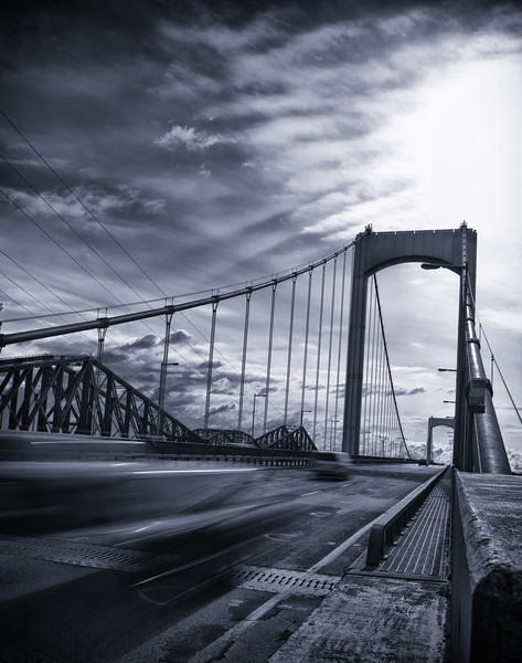 Bridge from canada with fast moving car on the road. Black and white with blue tint and vignetting added.
