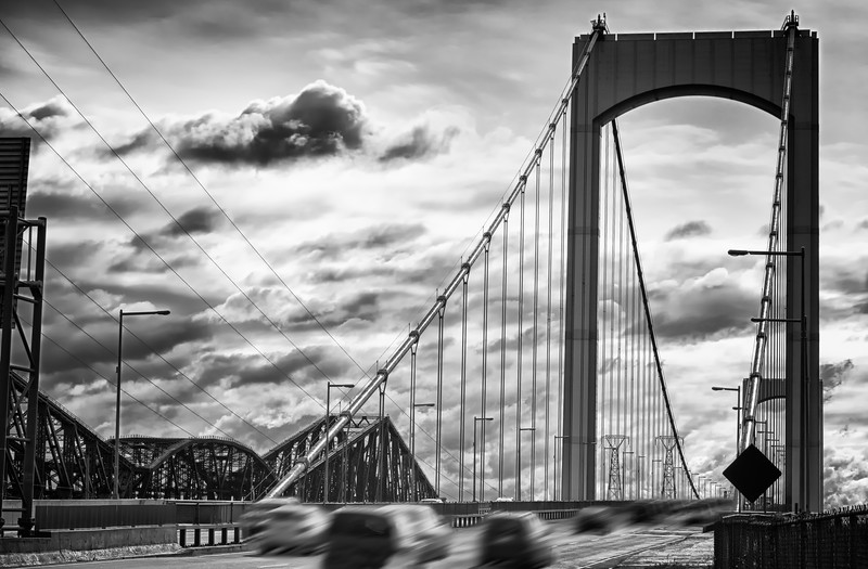Bridge from canada with fast moving car on the road. High contrast black and white with added vignetting.