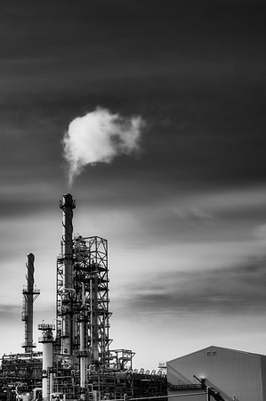 Oil refinery with smoke from the chemney.Black and white with high contrast.