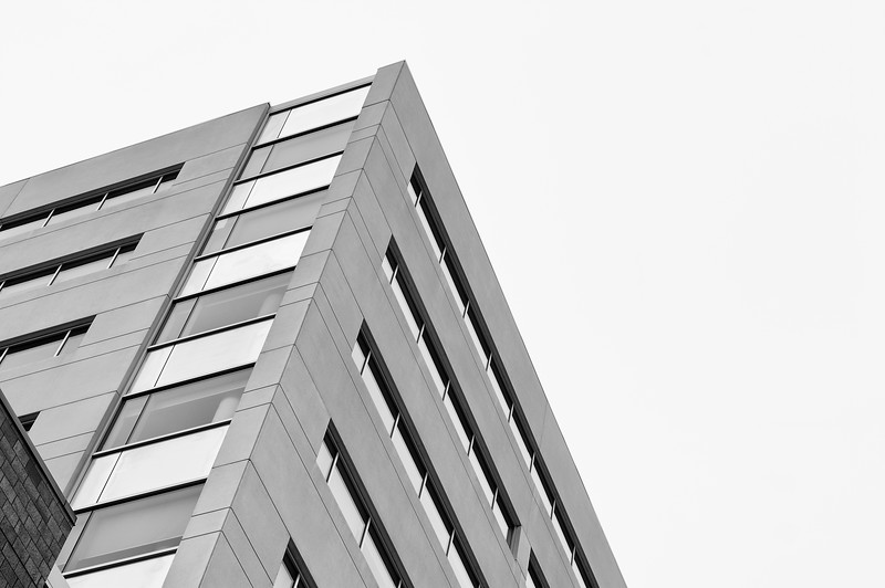 High rise top corner with white sky in the background. Black and white photography.