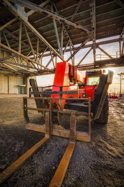 Industrial lift truck in a building site with structure and sun in the background.