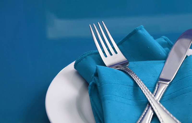 A colorful table set with plate, knife, fork and napkin