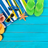 Beach scene with striped towel, sunglasses, flip flops, seashell and starfish laid on old weathered blue wood decking.  Space for copy.