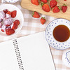 Strawberries and cream with blank recipe book or shopping list on a chopping board and check tablecloth.