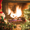 Christmas fireplace with roaring fire, decorated Christmas tree, and santa with sleigh on the hearth