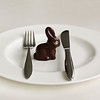 Chocolate Easter bunny sitting on a white plate surrounded by a fork and a knive.