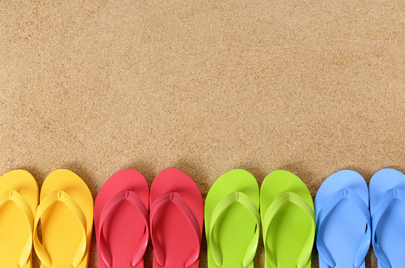 Flip flops in a row on a beach (studio shot - directional light and warm color are intentional).