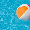 A single beach ball floating in a bright blue pool.