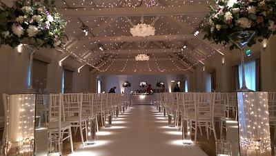The Ballroom set for a wedding ceremony, with our pealight canopy, fan shaped uplighter beams and the aisle illuminated with pinspots, later to be used for spot lighting the table centres
