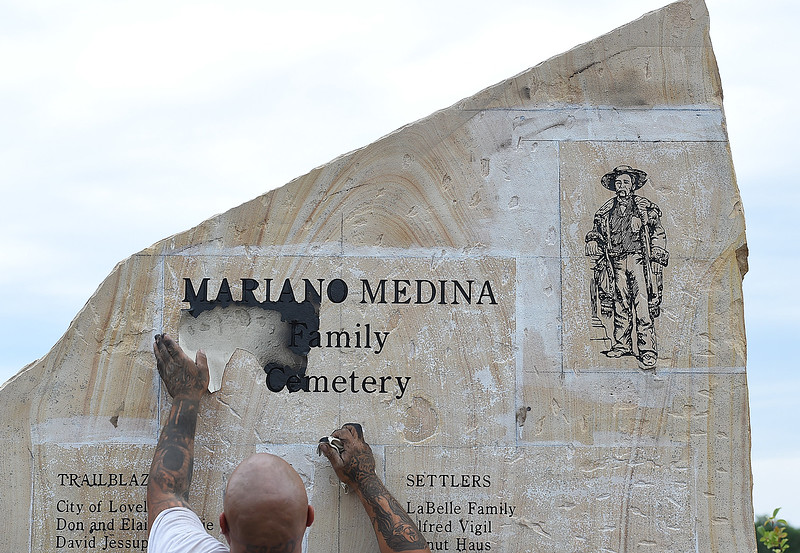 Ryan Barcelona with Rock Art by Carroll Enterprises, peels the stencil off of a stone after sandblasting and painting it Wednesday, July 12, 2017, at the Mariano Medina Family Cemetery in west Loveland. Larry Carroll, owner of Rock Art by Carroll Enterprises, donated his and Barcelona's  time and talent to engrave the stones near the cemetery for the Loveland Historical Society. Members of the hsitorical society watched in awe as the stones were engraved. Barcelona hand-sketched the historical drawing of Medina that they engraved on the piece.   (Photo by Jenny Sparks/Loveland Reporter-Herald)