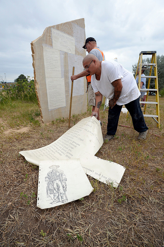 Ryan Barcelona, front, and Larry Carroll apply stencils to a stone Wednesday, July 12, 2017, at the Mariano Medina Family Cemetery in west Loveland. Larry Carroll, owner of Rock Art by Carroll Enterprises, donated his and Barcelona's time and talent to engrave the stones near the cemetery for the Loveland Historical Society. Members of the hsitorical society watched in awe as the stones were engraved. (Photo by Jenny Sparks/Loveland Reporter-Herald)
