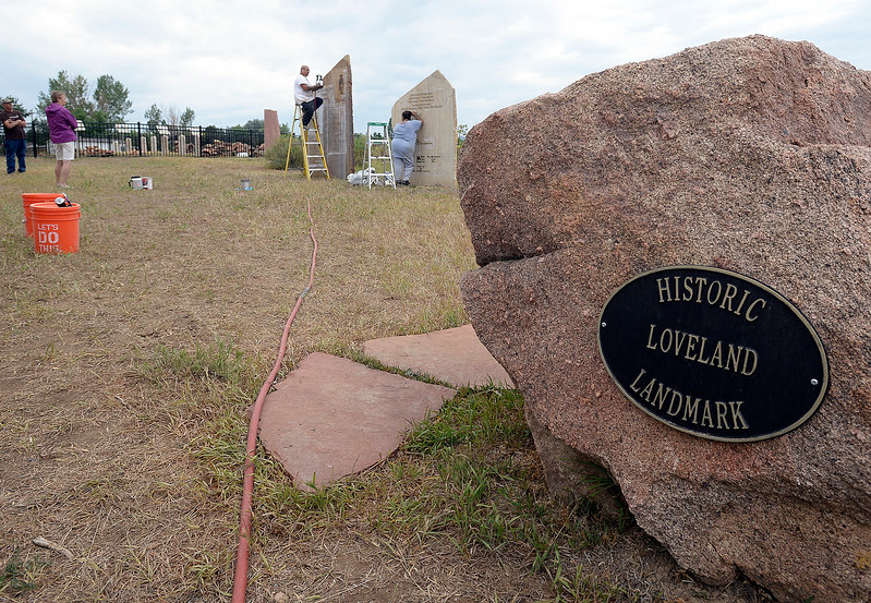Mike Perry, president of the Loveland Historical Society, far left, and Ann Ague, on the Mariano Medina Family Cemetery committee, far left, watch as Ryan Barcelona and Maria Barcelona peel stencils off of a stone Wednesday, July 12, 2017, at the Mariano Medina Family Cemetery in west Loveland. Larry Carroll, owner of Rock Art by Carroll Enterprises, donated his and Barcelona's  time and talent to engrave the stones near the cemetery for the Loveland Historical Society. Members of the hsitorical society watched in awe as the stones were engraved. (Photo by Jenny Sparks/Loveland Reporter-Herald)
