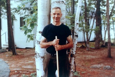 Charles Stone in front of birches, cabin #101