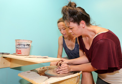 Laura Brees, at right, lends a hand to Emily Brooks at Stoneware Alchemy Clay Studio in Canton.  Photo by John Fitts
