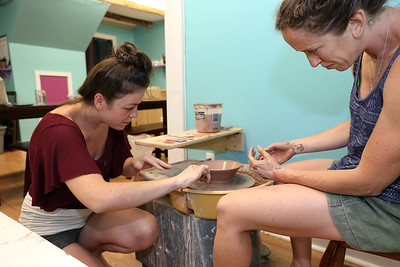 Laura Brees, at left, offers some advice to  Emily Brooks at Stoneware Alchemy Clay Studio in Canton.  Photo by John Fitts