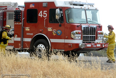 Firefighters with Engine 45 out of Durham stand by their enging as the Stoney Fire burns above Upper Bidwell Park seen from Hwy. 32 near Chico, Calif. Friday July 13, 2018. They said they had been on the fire most of the night.  (Bill Husa -- Enterprise-Record)