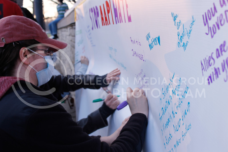 At the end of the vigil, community members were invited to come down and write a message of solidarity on a banner spread across the front of the stage in City Park. (Kaylie McLaughlin   Collegian Media Group)