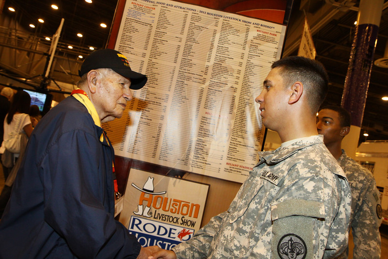 WWII Veterans participate in the Houston Livestock Show and Rodeo Armed Forces Appreciation Day. WWII veteran John Brown speaks with a curren service member.