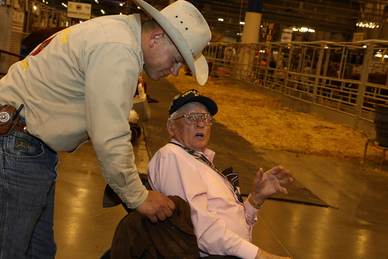WWII Veterans participate in the Houston Livestock Show and Rodeo Armed Forces Appreciation Day. Marine Mounted Guard Sgt. Cole assists WWII veteran Roy Hughes.