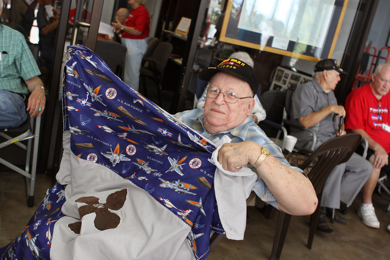 WWII Bennie W. shows off the quilt that Sandra made in honor of his service.