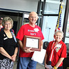 Anna Sims, Mavis Feldman, members of the Daughters of the American Revolution present Business owner Jack McClanahan with an award for his Patriotic display of the American flag.