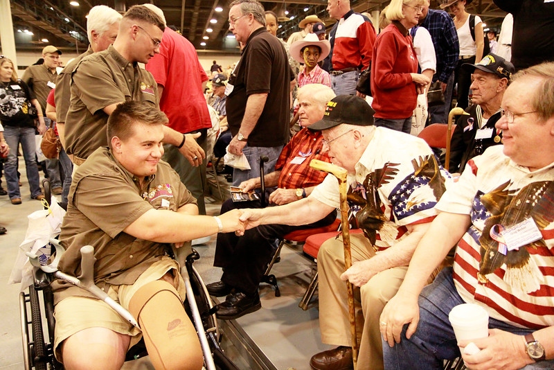 Wounded Warrior and member of Combat Marine Outdoors is greeted by WWII veterans.