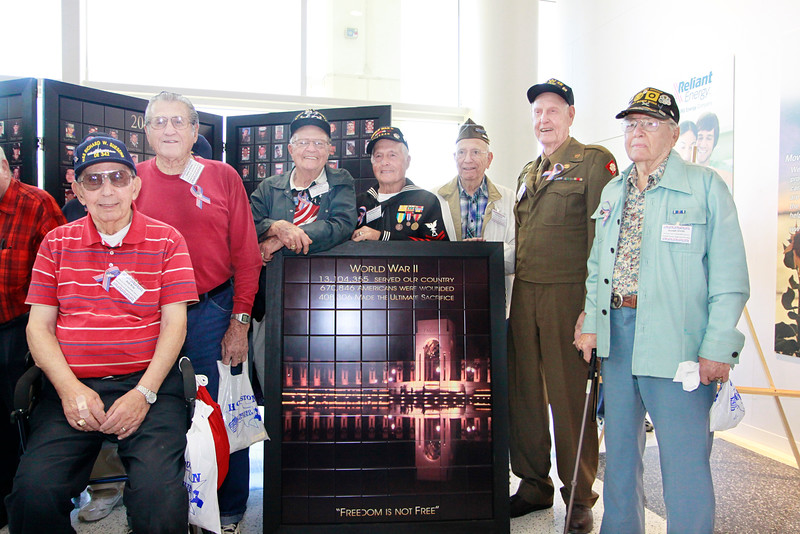 WWII veterans stand in honor of those remembered on the Texas Fallen Heroes Memorial Wall