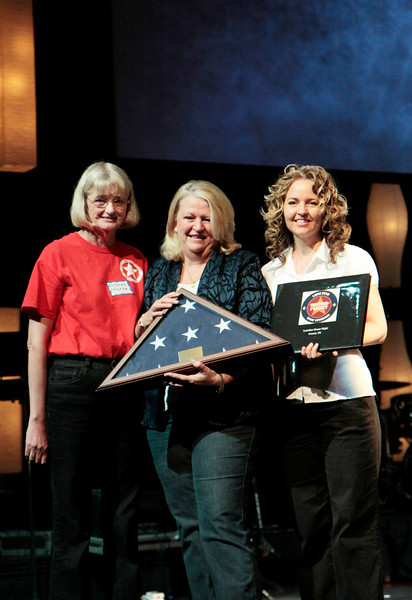 Organizer Dolores Morse and Honor Flight photographer Karie present Brenda Beavens with the Lone Star Honor Flight yearbook. <br /> <br /> Septembr 11, 2010. Lonestar Honor Flight showing of flight's 4 & 5.