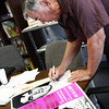 Heavy wieght champion Roy Harris autographs vintage posters for a fundraiser.