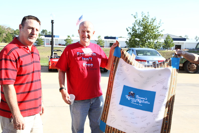 Sandra S. presents Buster Bowers with a handmade quilt to thank him for his support of local veterans. Buster has provided a free breakfast each month for the veterans.