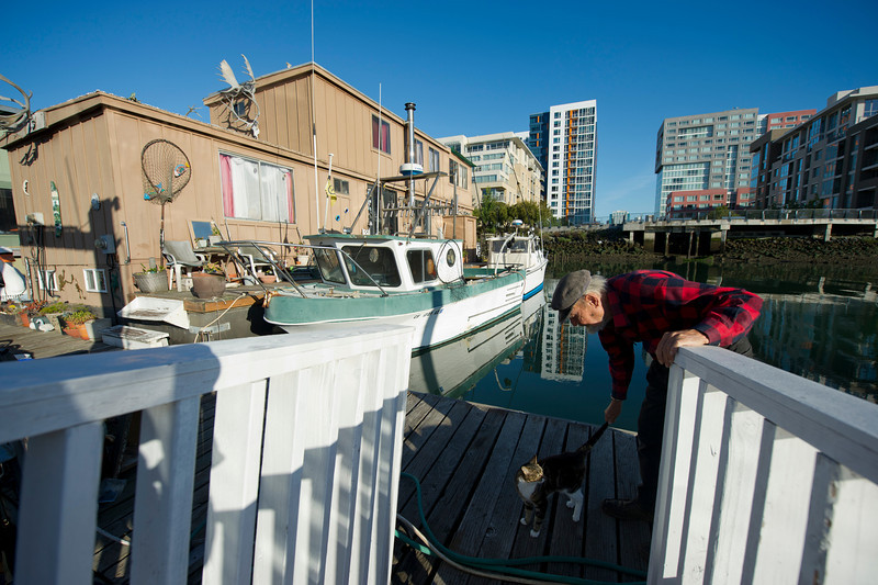 "Newly built high-rise apartment buildings loom in the background across Mission Creek Channel, as Ashley the cat looks at Srnka as he strokes her tail outside his houseboat, at left, in the early morning of Wednesday, June 6, 2012. ""Developers want this land, but we won that battle thanks to the Port Authority extending our lease,"" said Bob. He said he doesn't think residents are overly bitter now about the large developments surrounding the channel. ""I've started feeling claustrophobic, though,"" he added."