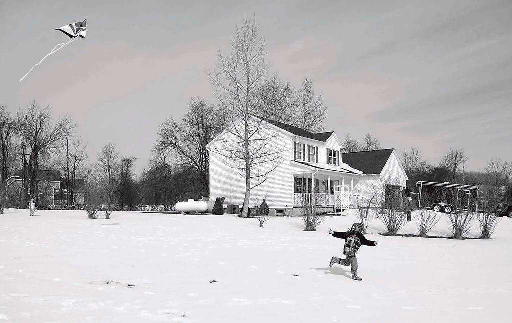 David Stankiewicz's grandson Michael Yerkey, 5, flies a kite in David's yard in McKean Township as the grownups of the family pack up the home on March 9, 2013. Andy Colwell/Erie Times-News