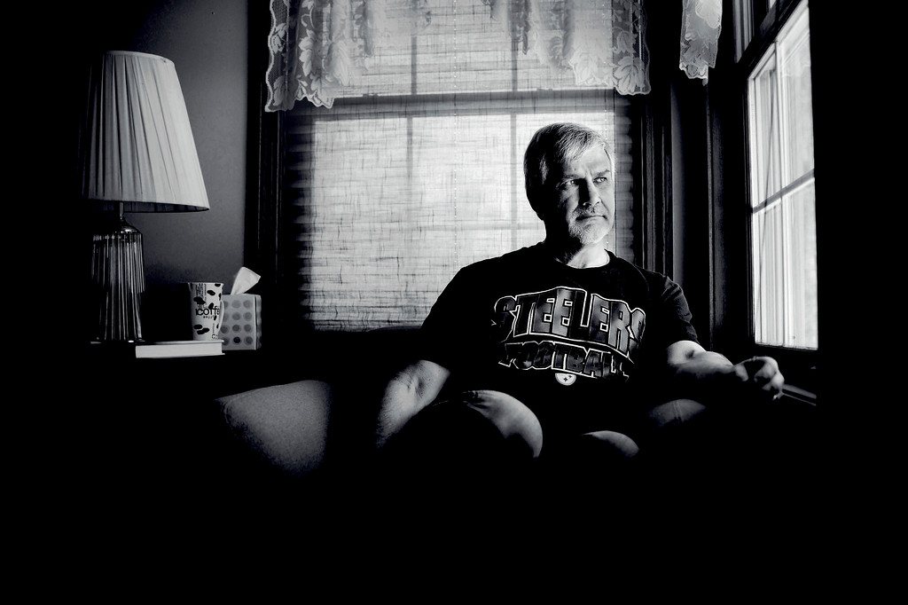 David Stankiewicz rests in his chair in his McKean Township house on Feb. 9, 2013, a month before he and his wife Lori Stankiewicz are scheduled to move from there to a new home in Erie. David finds solace in the vantage point and solitude provided by this corner seat as his life is consumed by his frontotemporal dementia at age 51. The rapidly progressing disease is similar to Alzheimer's disease and affects all aspects of his life, including moods, behavior and cognition. While his explanation for enjoying the chair deals with its landscape view and good light for reading, Lori adds that he'll also sit there when feeling frustrated or sad as a result of the dementia. Andy Colwell/Erie Times-News
