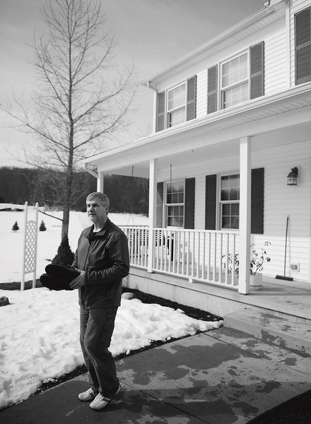 David Stankiewicz carries a last pair of shoes out of his McKean Township house on March 9, 2013, their last day in the house. Andy Colwell/Erie Times-News