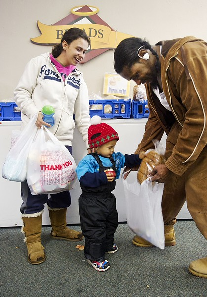 Racheal Wheaton, 24, left, laughs as her two-year-old son Michael Griffiths puts a loaf of bread in a bag held by Al-Mujahideen Sirrajuldeen Siffullah Muhammad Ibin Henrun, 48, who is an Erie City Mission Family Care Center volunteer working at the center in Erie on Nov. 13. ANDY COLWELL/